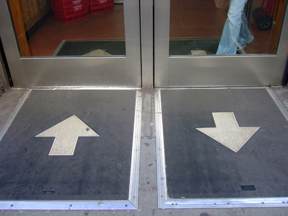 Sensors on mat detect feet of individuals about to enter/exit the store, and doors slide open accordingly